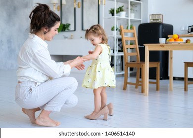 Beautiful mother and little daughter have fun in a bright and spacious apartment. The baby is trying on her mother's high-heeled shoes. Mom is a young brunette in white clothes, a girl in a dress.