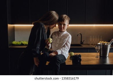 Beautiful Mother and Little Son in Modern Kitchen. Caucasian Woman in Black Dress. Blond Boy Sit on Table, Hold Apple. Happy Family Medium Shot. Child in White Shirt Looking at Camera