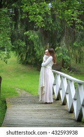 beautiful mother in a long dress hugging his son on a wooden bridge in the park bridge