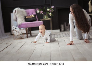 Beautiful mother with long hair and baby crawling together on the floor, lifestyle and motherhood in a real Scandinavian-style interior.