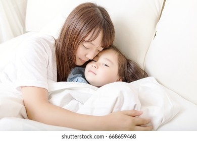 Beautiful mother and lovely daughter are laughing happily in bed