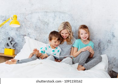 Beautiful mother is reading a story to her children
