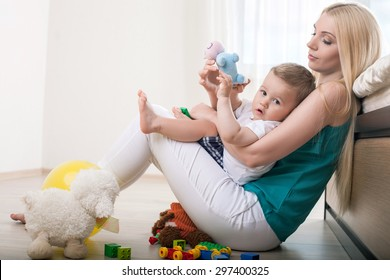 Beautiful mother is sitting on flooring and holding her small son. She is hugging him with love. The boy is holding a toy and looking at the camera with interest