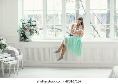 beautiful mother in soft blue skirt and a denim shirt breastfeeding her baby while sitting on the windowsill next to flowers