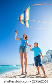 Beautiful mother and son holding arms with kite