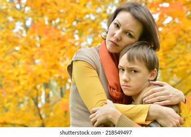 Beautiful mother with a son on a walk during the fall of the leaves in the park