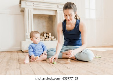 Beautiful mother and son sitting on wooden floor and playing with wooden toys at home