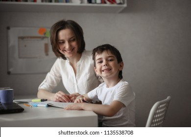 beautiful mother teaches her son at home at the table, real interior