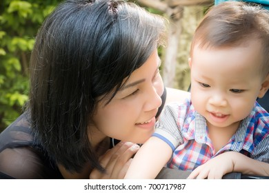 A beautiful mother is teaching her son. The kid is enjoying some lesson and gets happy with beautiful sunlight at a park