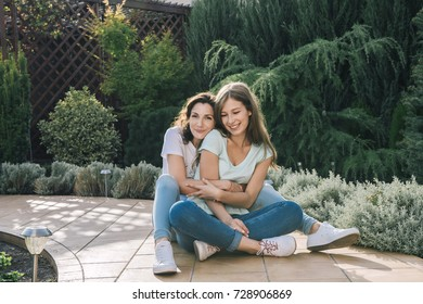 Beautiful mother with teenage daughters sitting in garden near home.