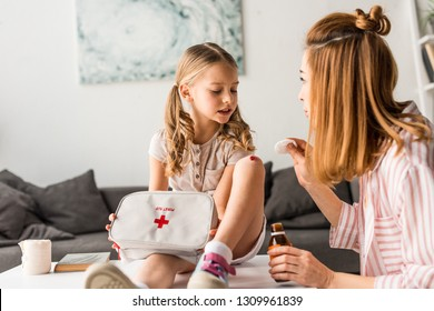 Beautiful mother treating injured daughter with antiseptic at home