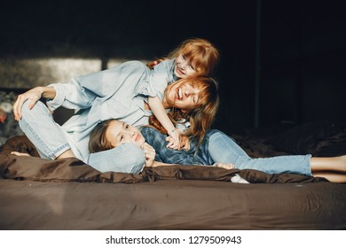 Beautiful mother with two daughter. Family sitting in the room on a bed.