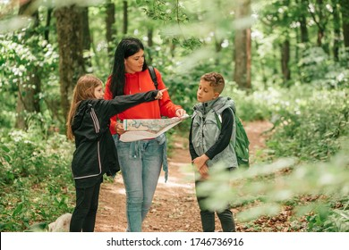 Beautiful mother with two kids are walking through forest, using a map and planning a hiking adventure. Happy family having fun together.