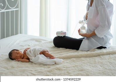 Beautiful mother use automatic breast pump to get breast milk and sitting near the sleeping newborn on white bed with white curtain  background and day light. Concept of  love and warming emotion.