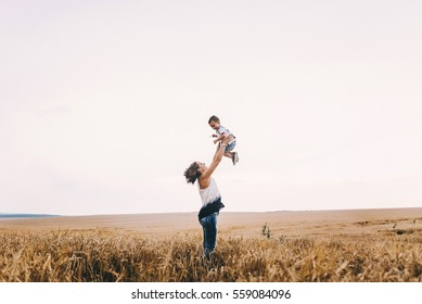 beautiful mother young son walking in wheat field. mother tenderly touches her son's hair, holding hands, hugs and throws up in the sky. mother's love