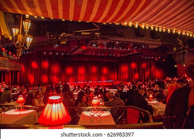 Beautiful Moulin Rouge interior design with many small tables, red lamps and a stage in the middle of the room. Very classic and stylish. Beautiful Moulin Rouge in Paris, France , October 10, 2014.