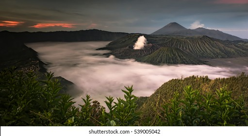 Beautiful Mount Bromo landscape view in sunrise misty morning with dramatic clouds and Semeru volcano background.