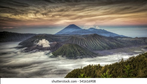 Beautiful Mount Bromo landscape view in sunrise misty morning with beautiful clouds background.