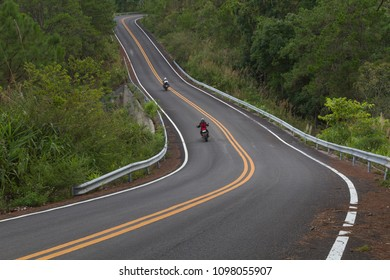Beautiful mountain asphalt road with curve and double yellow line, bikers riding big motorbike, moto trip in Thailand