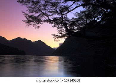 Beautiful mountain lake during sunset in Fiordland National Park, South Island, New Zealand