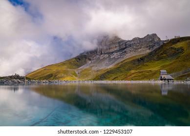 A beautiful mountain lake in Kleine Scheidegg with the Eiger North Face hidden behind clouds in the background in the alpine region of Grindelwald, Switzerland.