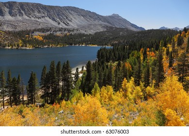 A beautiful mountain lake with turquoise and blue water, surrounded by yellow and green trees