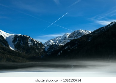 Beautiful mountain landscape with early morning fog on Anterselva - Antholzer See frozen lake in Val Pusteria, South Tyrol -Südtirol, Italian Alps in wintertime. Snow and sunny day with clear blue sky