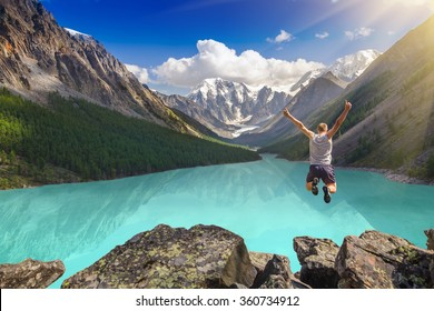 Beautiful mountain landscape with lake and jumping man. Leap from the cliff. Extreme Sport.