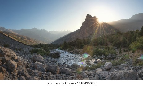 Beautiful mountain landscape. Scenic river in mountains. Mountains nature in the morning with bright sun rays behind summit
