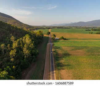 Beautiful mountain landscape with sugar cane fields foreground. Dramatic DRONE aerial view of fields, trees, green forest, farm, mountains, blue sky & road. Shot in Walsh's Pyramid, Cairns, Australia.