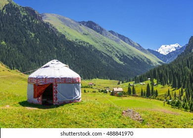 Beautiful mountain landscape with the white Yurt, decorated with a red ornament, Kyrgyzstan.