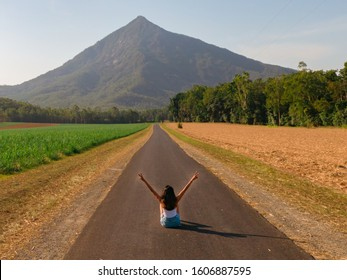 Beautiful mountain landscape & Woman with sugar cane fields foreground. Dramatic DRONE aerial view of fields, trees, green forest, farm, mountains & road. Shot in Walsh's Pyramid, Cairns, Australia.
