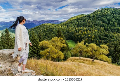A beautiful mountain landscape. Yellow grass, fir forest and mountains. A girl dressed in white admires this beautiful autumnal decor. Beginning of autumn. The young woman admires the landscape.