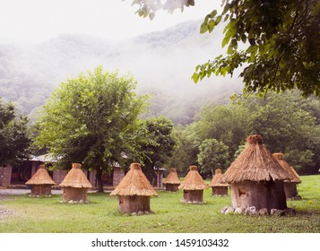 Beautiful mountain morning misty landscape with an apiary. Wooden beehives with thatched-roof stand against a background of trees and mountains in the clouds.