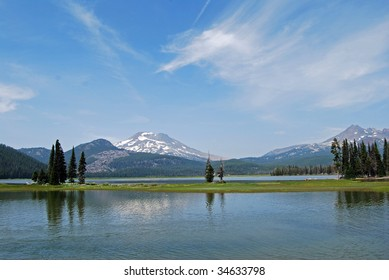 beautiful mountain peaks in central oregon behind a calm lake