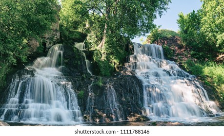 Beautiful mountain rainforest waterfall with fast flowing water and rocks, long exposure. Natural seasonal travel outdoor background in hipster vintage style