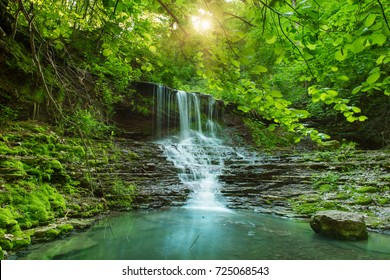 Schöner Bergregenwald Wasserfall mit schnell fließendem Wasser und Felsen, lange Exposition. Natürliche Jahreszeit-Reise im Freien Hintergrund mit Sonnenschein