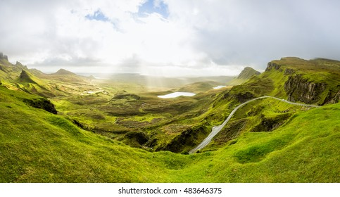 Beautiful mountain range in Scotland. View from the top of Quiraing into the green Valley. Sun beams break through a heavy cloud cover.
