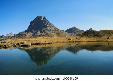 Beautiful mountain reflecting in calm water.  Pic du Midi d'Ossau 2884 m at Lac Roumassot (Lacs d'Ayous), Parc national des Pyrenees, Pyrenees-Atlantiques, Aquitaine, France.