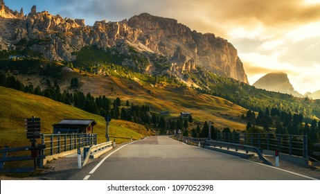 Beautiful mountain road with trees, forest and mountains in the backgrounds. Taken at state highway road of Passo Gardena in Dolomites mountain in Italy.