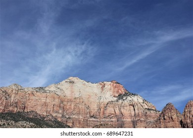 Beautiful mountain scene with a backdrop of wispy white clouds in a deep blue sky