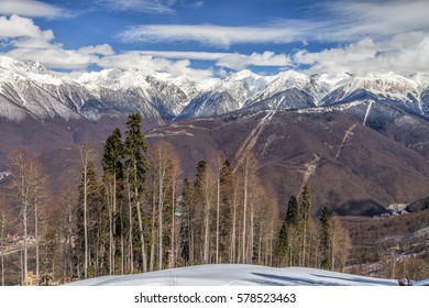 Beautiful mountain scenic winter landscape of the Main Caucasian ridge with snowy peaks, blue sky with clouds and trees on the foreground,