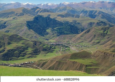 Beautiful mountain summer landscape. Scenic view of the terraced fields, green valley with village on a background of the snow-covered Caucasus Mountains. Nature and travel. North Caucasus, Dagestan