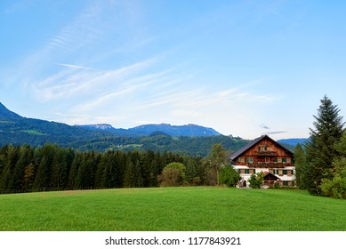 Beautiful mountain valley/field landscape with blue sky and forest in Austrian Alps. Austria, Salzkammergut. Traditional mountain house in Austrian Alps