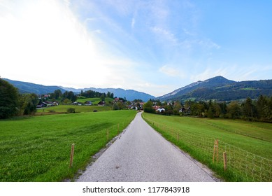Beautiful mountain valley/field road landscape with forest, traditional austrian village and blue sky in Austrian Alps. Austria, Salzkammergut