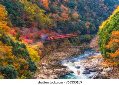 beautiful mountain view in autumn season with sagano scenic railway or romantic train on bridge and boat in the river in Arashiyama, Kyoyo, Japan, soft focus