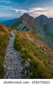 Beautiful mountain walkway surrounded by fresh grass and leading to the high rocky mountain. High Tatras NP, Slovakia
