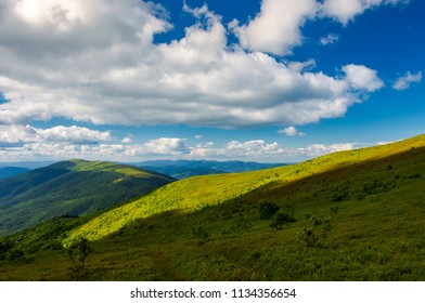 beautiful mountainous landscape under the summer sky. fluffy clouds over the mountain ridge. light on the nearest hill. pleasant atmosphere and good day for a hike. lovely nature background