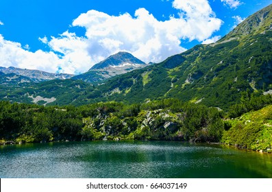 Beautiful mountains lake with a reflection of the high green mountains peaks, on the blue sky background. Amazing Mountain hiking paradise landscape with a lake, no people.