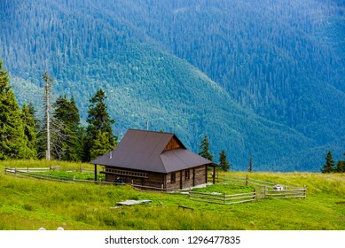 Beautiful mountains landscape with green meadow and modern wooden house